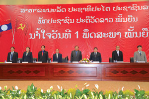 Mr Bounnhang Vorachit (fourth right), high level Party and government officials and other invited guests stand for the national anthem at the meeting.