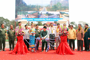 Lieutenant General Douangchay Phichit cuts a ribbon to open the new road.
